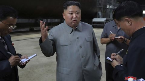 """In this undated photo provided on Tuesday, July 23, 2019, by the North Korean government, North Korean leader Kim Jong Un, center, speaks while inspecting a newly built submarine to be deployed soon, at an unknown location in North Korea. North Korean state media's report on Tuesday comes days after North Korea said it may lift its 20-month suspension of nuclear and missile tests to protest expected military drills between the United States and South Korea. Independent journalists were not given access to cover the event depicted in this image distributed by the North Korean government. The content of this image is as provided and cannot be independently verified. Korean language watermark on image as provided by source reads: """"KCNA"""" which is the abbreviation for Korean Central News Agency. (Korean Central News Agency/Korea News Service via AP)"""