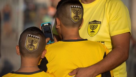"""Supporters of Israeli football club Beitar Jerusalem enter the stadium bearing the club's shield on their heads prior to their return match against Belgium team Charleroi on July 23, 2015 at Teddy Stadium in Jerusalem. Beitar Jerusalem owner Eli Tabib announced after the first leg of Europa League match between Charleroi and Beitar was halted in Belgium that he was """"ashamed"""" by the conduct of an """"extremist group of fans"""" and intended to sell the team. AFP PHOTO / MENAHEM KAHANA        (Photo credit should read MENAHEM KAHANA/AFP/Getty Images)"""
