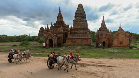 <strong>Bagan, Myanmar: </strong>Tourists riding bull carts pass a Buddhist temple in the ancient city of Bagan.