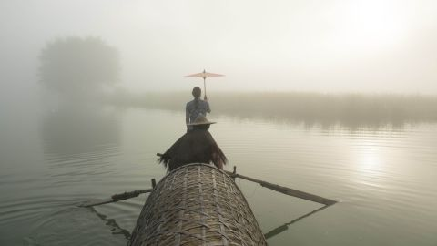 """<strong>Xiaya Town, China: </strong>Husband-and-wife team Tang Linglong and Shao Zhulian work as """"fishing models,"""" demonstrating traditional fishing methods in picturesque surroundings for the benefit of photography enthusiasts."""