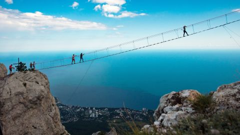 <strong>Yalta, Crimean Mountains: </strong>Brave souls cross a hanging bridge linking the two peaks of Ai-Petri Mountain, famously one of the windiest places in the region.
