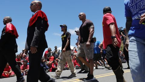 """Actor Dwayne """"The Rock"""" Johnson, third from right, walks with telescope protesters during his visit to the base of Mauna Kea."""