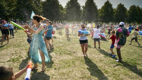 People cool off with a water fight at a park in The Hague, Netherlands, on Wednesday, July 24.