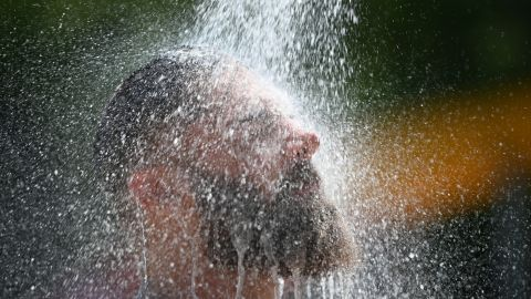 A man cools down at an outdoor pool's shower in Baden-Wuerttemberg, Germany, on Thursday, July 25.
