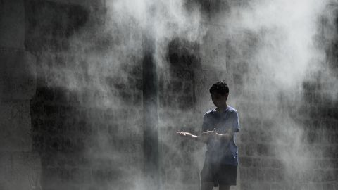 A boy cools off under a public water spray on the bank of the Seine river in Paris on Thursday, July 25.
