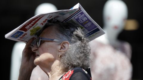 A woman shields herself with a newspaper in Milan, Italy, on Thursday, July 25.