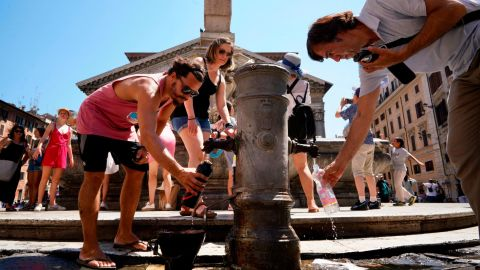 People collect water from the public fountain in front of the Pantheon in Rome on Thursday, July 25.