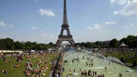 People cool off and sunbathe next to the Eiffel Tower in Paris on Thursday, July 25.