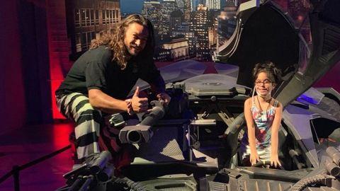 Jason Momoa and a young fan hop into the Batmobile.