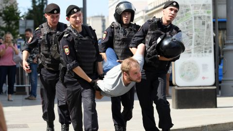 Police officers detain a man during an unauthorized rally demanding free and fair elections outside the mayor's offices in Moscow on July 27, 2019.