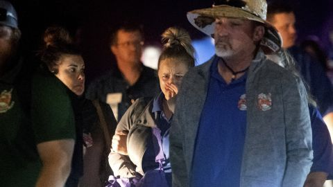 A woman reacts as she and others are escorted from the park.