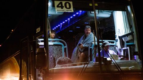 Jane and Edward Jacobucci wait on a chartered bus after leaving the festival area.