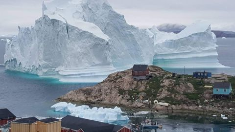 A picture taken on July 13, 2018 shows an iceberg behind houses and buildings after it grounded outside the village of Innarsuit, an island settlement in the Avannaata municipality in northwestern Greenland. (Photo by MAGNUS KRISTENSEN / Ritzau Scanpix / AFP) / Denmark OUT        (Photo credit should read MAGNUS KRISTENSEN/AFP/Getty Images)