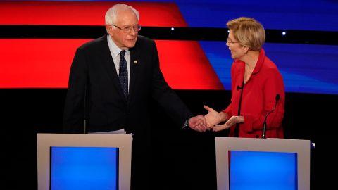 Sanders grabs the hand of US Sen. Elizabeth Warren during the Democratic debates in Detroit in July 2019.