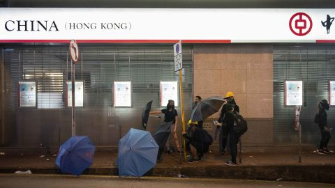 Protesters stand next to a Chinese state-owned commercial banking company Bank of China during the clashes.