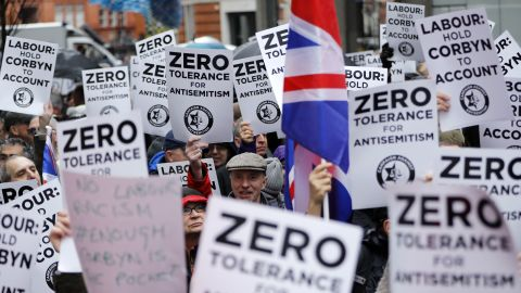 People hold up placards and Union flags as they gather for a demonstration against anti-Semitism.