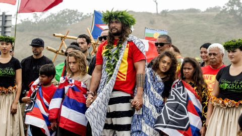 Actor Jason Momoa holds the hands of his children, Nakoa-Wolf Momoa, left, and Lola Momoa, right, as he is welcomed with a hula while visiting elders and Native Hawaiian protesters blocking the construction of a giant telescope on Hawaii's tallest mountain, at Mauna Kea Access Road on Wednesday, July 31, 2019, in Mauna Kea, Hawaii.  (Hollyn Johnson/Hawaii Tribune-Herald via AP)