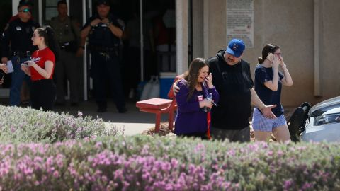 People gather at MacArthur Elementary School in El Paso, looking for family and friends. The school was being used as a reunification center.