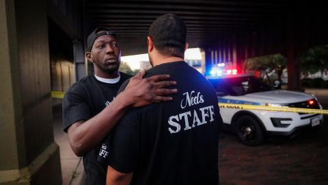 Witnesses comfort one another at the scene in Dayton on Sunday.