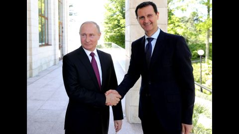 Putin shakes hands with Syrian President Bashar al-Assad during their meeting in Sochi in May 2018.