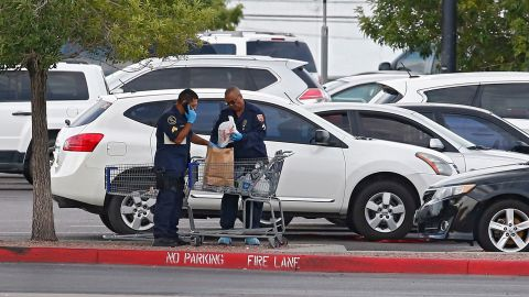 Police conduct their investigation in the parking lot of an El Paso Walmart on Sunday.