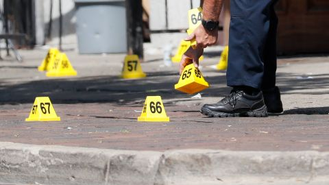 Authorities remove evidence markers at the scene of a mass shooting, Sunday, Aug. 4, 2019, in Dayton, Ohio. Multiple  people in Ohio have been killed in the second mass shooting in the U.S. in less than 24 hours, and the suspected shooter is also deceased, police said. (AP Photo/John Minchillo)