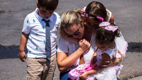 Cristina Zapata and her children pay their respects to the victims of the El Paso shooting.
