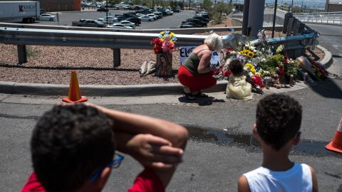 People pay their respects to the victims of the El Paso shooting at a makeshift memorial across from the Walmart near the Cielo Vista Mall.