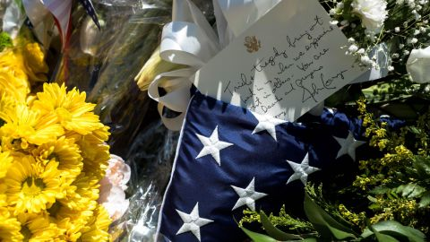 A flag and letter signed by US Sen. John Cornyn is seen on flowers at a makeshift memorial in El Paso.