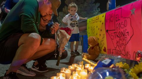 Mourners pray at a makeshift memorial for the victims of the El Paso shooting.