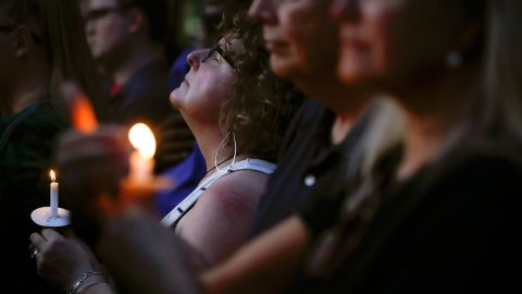 Mourners pause for a prayer in Dayton.