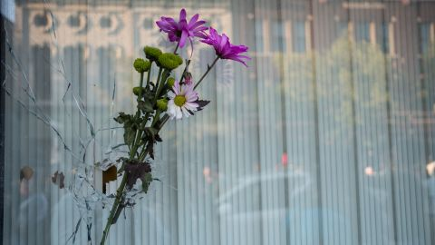 Flowers are placed in a bullet hole a few buildings away from where the shooting took place in Dayton.