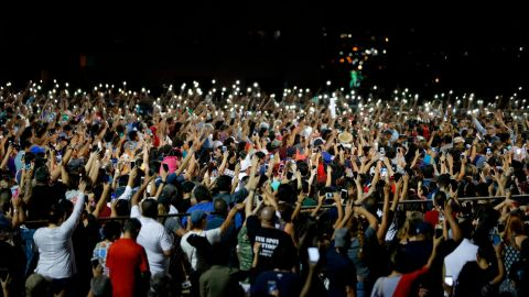People raise their arms in the air Sunday during a vigil for the El Paso victims.