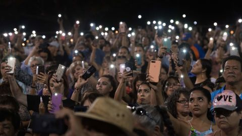People hold up their phones during a prayer and candle vigil organized by the city, after a shooting left 20 people dead at the Cielo Vista Mall Wal-Mart in El Paso, Texas, on August 4, 2019. - The United States mourned Sunday for victims of two mass shootings that killed 29 people in less than 24 hours as debate raged over whether President Donald Trump's rhetoric was partly to blame for surging gun violence. The rampages turned innocent snippets of everyday life into nightmares of bloodshed: 20 people were shot dead while shopping at a crowded Walmart in El Paso, Texas on Saturday morning, and nine more outside a bar in a popular nightlife district in Dayton, Ohio just 13 hours later. (Photo by Mark RALSTON / AFP)        (Photo credit should read MARK RALSTON/AFP/Getty Images)