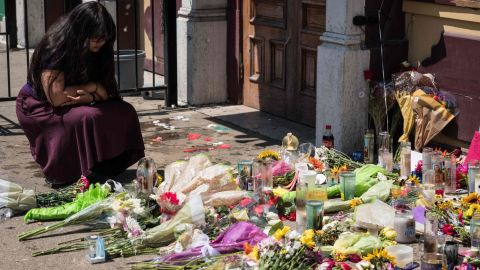 A woman kneels near candles and flowers placed outside Ned Peppers.