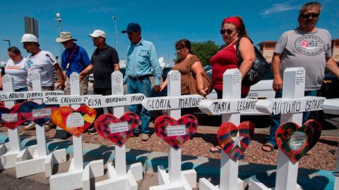 """People pray beside crosses with the names of victims who died in the shooting to a makeshift memorial after the shooting that left 22 people dead at the Cielo Vista Mall WalMart in El Paso, Texas, on August 5, 2019. - US President Donald Trump on Monday urged Republicans and Democrats to agree on tighter gun control and suggested legislation could be linked to immigration reform after two shootings left 30 people dead and sparked accusations that his rhetoric was part of the problem. """"Republicans and Democrats must come together and get strong background checks, perhaps marrying this legislation with desperately needed immigration reform,"""" Trump tweeted as he prepared to address the nation on two weekend shootings in Texas and Ohio. """"We must have something good, if not GREAT, come out of these two tragic events!"""" Trump wrote. (Photo by Mark RALSTON / AFP)        (Photo credit should read MARK RALSTON/AFP/Getty Images)"""