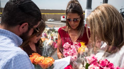 Claudia Portillo, 52, second from right, prays Tuesday near the site of the Walmart shooting.