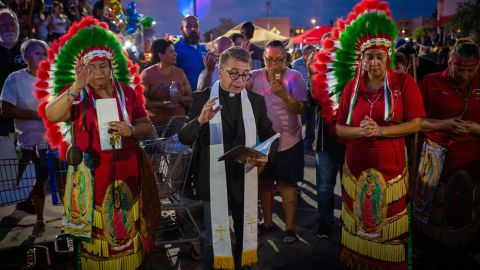 Members of the Apache tribe stand alongside a priest during a vigil in El Paso.