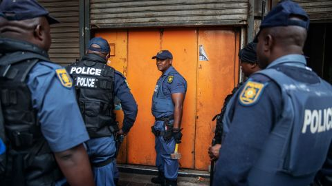 Police officers  in Johannesburg stand outside a locked shop allegedly containing counterfeit goods.