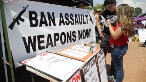 """A """"Ban Assault Weapons Now"""" sign is displayed near a voter registration table in El Paso."""