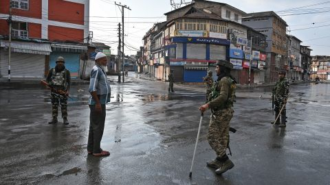 Indian security personnel question a man on a street during a curfew in Srinagar on August 8, 2019.