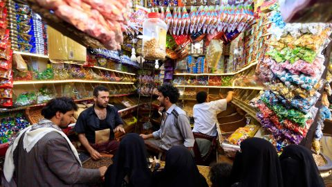 Yemenis buy sweets and nuts at a market in the capital Sanaa on August 8, 2019, as Muslims prepare to celebrate Eid al-Adha.