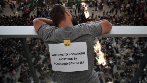 A man looks out from the departures area as protesters rally in arrivals against a controversial extradition bill at Hong Kongs international airport on August 9, 2019. - Hundreds of pro-democracy activists, some wearing face masks and helmets, staged a sit-in at Hong Kong's airport on August 9 hoping to win support from international visitors for their movement. (Photo by Anthony WALLACE / AFP)        (Photo credit should read ANTHONY WALLACE/AFP/Getty Images)