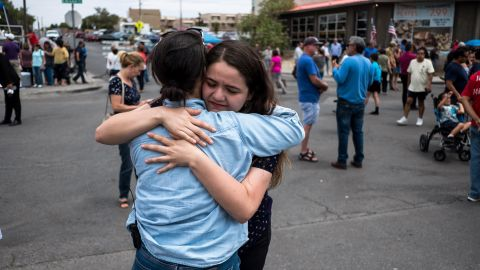 CNN reporter Nicole Chavez hugs Adria Gonzalez, a survivor of the mass shooting in El Paso, nearby a memorial, across from the Walmart where the shooting took place, in El Paso, Texas, Tuesday, Aug. 6, 2019.