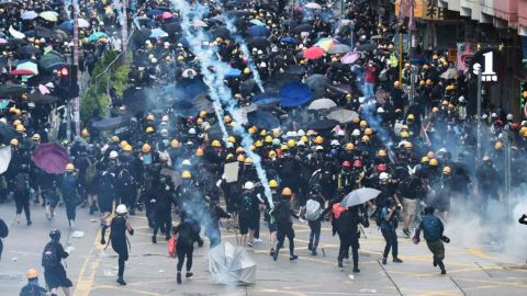 Protesters throw back tear gas fired by the police during a demonstratrion in Sham Shui Po district in Hong Kong on August 11, 2019.