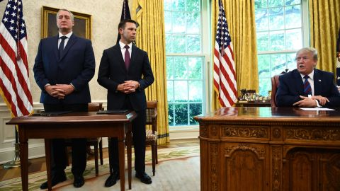 US President Donald Trump speaks to the media as Guatemalan minister of Interior and Home Affairs Enrique Degenhart (L) and Acting US Department of Homeland Security Secretary Kevin McAleenan look on after signing an asylum agreement in the Oval Office of the White House in Washington, DC on July 26, 2019. (Photo by Brendan Smialowski / AFP)