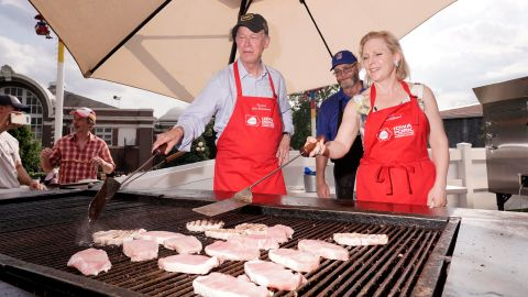 Democratic presidential candidates John Hickenlooper and Kirsten Gillibrand flip pork chops at the Iowa State Fair on Saturday, August 10. Iowa is the top pork-producing state in the United States.