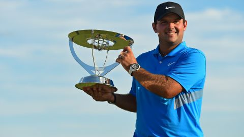 Patrick Reed celebrates with the The Northern Trust's winner's trophy.