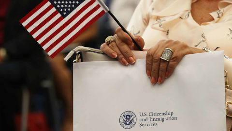 MIAMI, FL - AUGUST 17:  A person holds an American flag as they participate in a ceremony to become an American citizen during a U.S. Citizenship & Immigration Services naturalization ceremony at the Miami Field Office on August 17, 2018 in Miami, Florida. The ceremony included 141 citizenship candidates that originated from the following 33 countries: Argentina, Brazil, Bulgaria, Cameroon, Chile, Colombia, Costa Rica, Cuba, Dominican Republic, Ecuador, El Salvador,  France, Grenada, Guatemala, Haiti, Honduras, Hungry, Israel, Italy, Jamaica, Jordan, Lithuania, Mexico, Nicaragua, Nigeria, Phillippines, Slovakia, Spain, Ukraine, United Kingdom, Uruguay, Uzbekistan and Venezuela.  (Photo by Joe Raedle/Getty Images)
