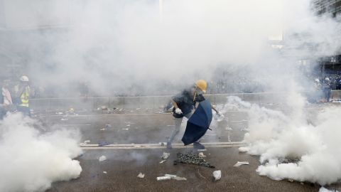 A protester douses a tear gas canister with water outside the Legislative Council during a protest against a proposed extradition law in Hong Kong, China.